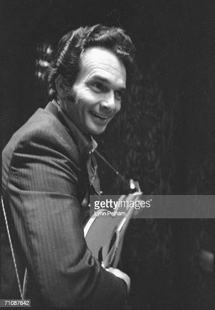 American country music performer Merle Haggard smiles as he plays an acoustic guitar 1970