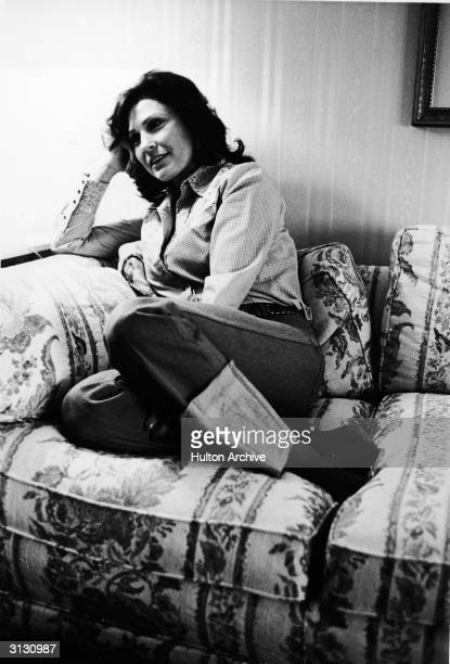 American country music singer and guitarist Loretta Lynn sits on a sofa with her legs curled under her and her head on her hand 1979