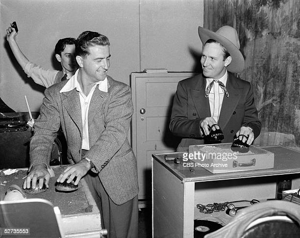 American country music singer Gene Autry right creates the sound of a galloping horse alongside foley artists during a broadcast of the CBS radio...