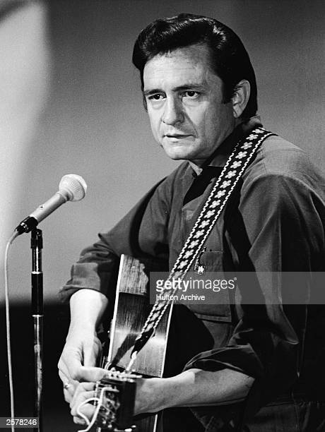 American country singer and songwriter Johnny Cash plays acoustic guitar in a still from his television variety series 'The Johnny Cash Show' circa...