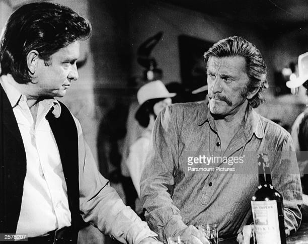 American country singer Johnny Cash and actor Kirk Douglas stand at a bar in a still from the film 'A Gunfight' directed by Lamont Johnson New Mexico...