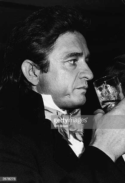 American country singer Johnny Cash has a drink while attending the Bob Hope benefit dinner for the Eisenhower Medical Center held at the Waldorf...