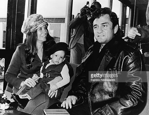 American country singer Johnny Cash sits inside an airport with his wife June Carter Cash and their infant son John Carter Cash as the singer arrived...
