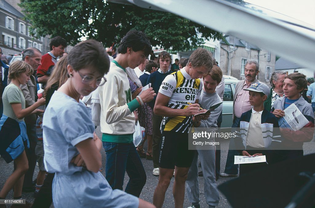 American cyclist <a gi-track='captionPersonalityLinkClicked' href=/galleries/search?phrase=Greg+LeMond&family=editorial&specificpeople=504953 ng-click='$event.stopPropagation()'>Greg LeMond</a> (centre-right) signs autographs at the Critérium de Château-Chinon road race, Château-Chinon, Nièvre, France, circa 1982.