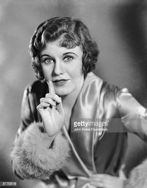 American dancer and actress Ginger Rogers puts her finger to her lips in a silencing gesture