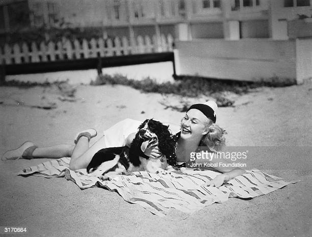 American dancer and actress Ginger Rogers stretches out on a beach towel with her pet spaniel