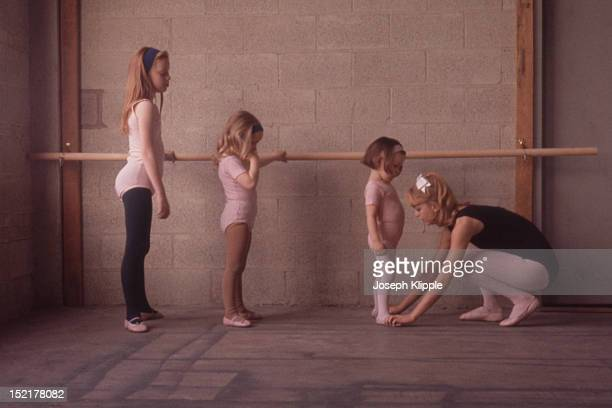 American dancer and dance instructor and future actress Goldie Hawn adjusts the feet of one of her young ballet students Washington DC 1964