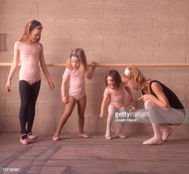 American dancer and dance instructor and future actress Goldie Hawn examines the foot positions of her young ballet students Washington DC 1964