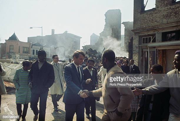 American Democratic Party politician and Senator from New York Robert F Kennedy shakes hands with local residents as he visits riot damaged...