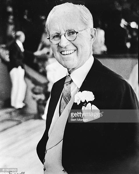 American diplomat and financier Joseph P Kennedy Sr in a tuxedo and boutonniere smiles as he attends the wedding of his son John F Kennedy to...