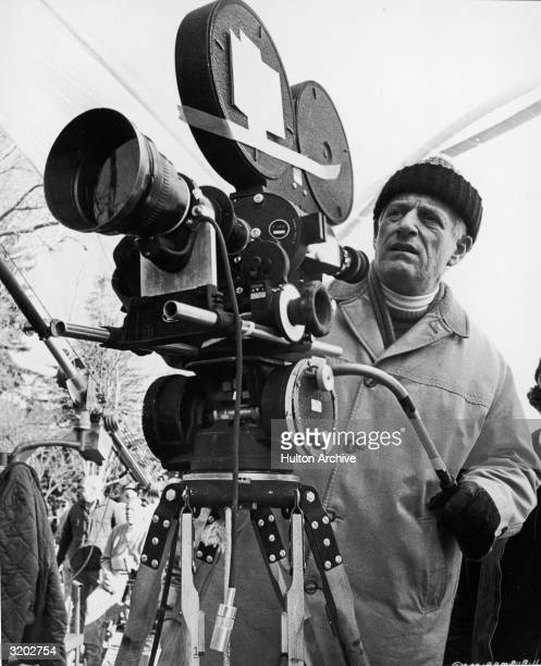 American director and producer Stanley Kramer stands behind a motion picture camera outdoors on the set of his film 'RPM' Kramer wears a winter coat...