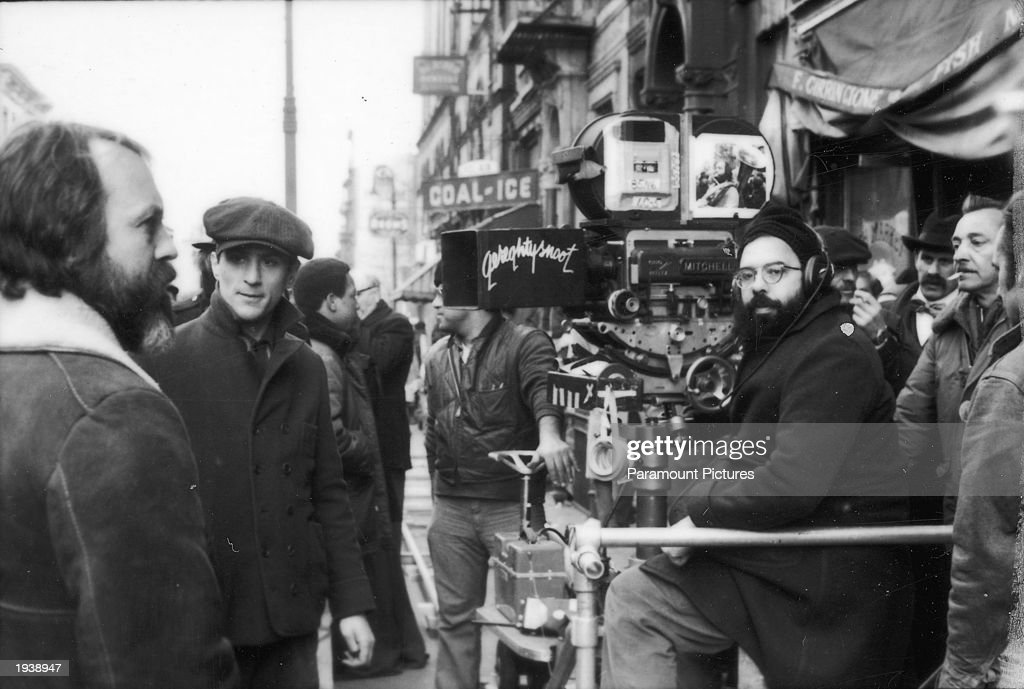 American director Francis Ford Coppola sitting with the camera on the set of his film 'The Godfather Part II' 1974 Robert DeNiro is standing at left