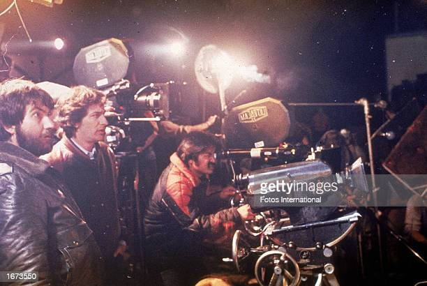 American director Tobe Hooper lenses a shot behind the camera as producer and codirector Steven Spielberg and other crew members stand by on the set...