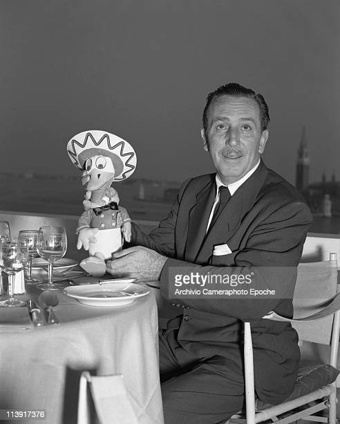 American director Walt Disney sitting on a restaurant terrace and holding a Donald Duck with sombrero puppet Venice 1951