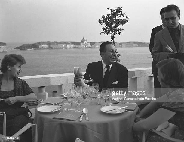 American director Walt Disney wearing a suit and a tie and holding a doll portrayed while sitting at the Danieli's restaurant table with guests and...
