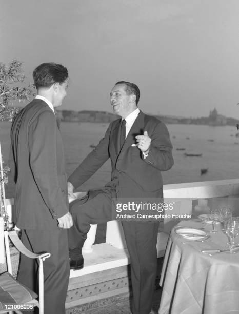 American director Walt Disney wearing a suit and a tie and smoking a cigarette portrayed while chatting with a man at Danieli's restaurant terrace...