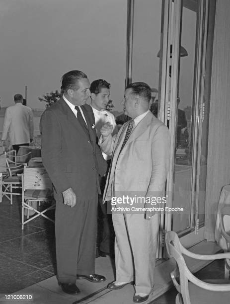 American director Walt Disney wearing a suit and a tie portrayed while chatting with a man smoking a cigarette at Danieli's restaurant terrace Venice...