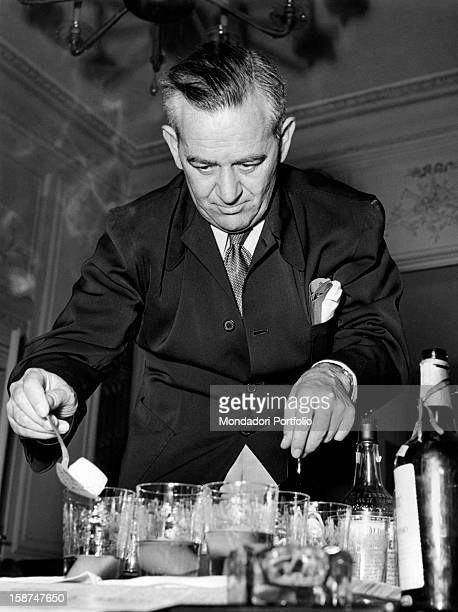 American director William Wyler pouring himself a drink at the Grand Hotel in Rome during the press conference for the presentation of his next film...