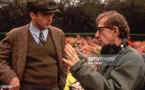 American director Woody Allen gestures with his hand while directing American actor John Cusack outdoors on the set of his film 'Bullets over...