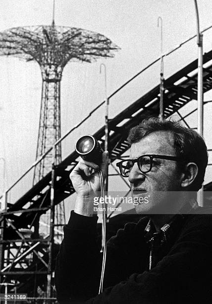 American director Woody Allen holds a viewfinder in front of the Cyclone rollercoaster at Coney Island on the set of his film 'Annie Hall' Brooklyn...
