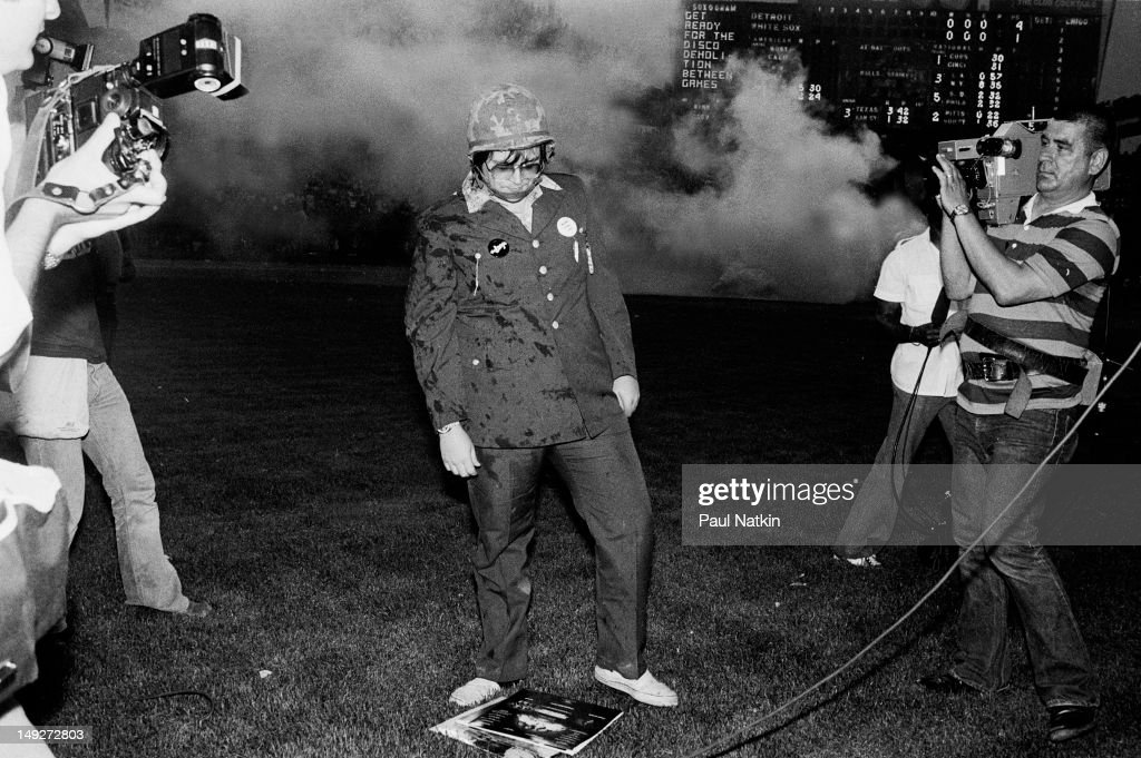 American disc jockey Steve Dahl stares at a pile of records on the field during an antidisco promotion at Comiskey Park Chicago Illinois July 12 1979...