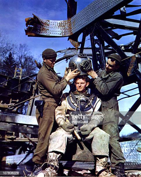 American diver Michael O'Brien is helped into his dive suit by Albert Boettner and EL Kennedy all from the 1058 Port Construction Company near Aachen...