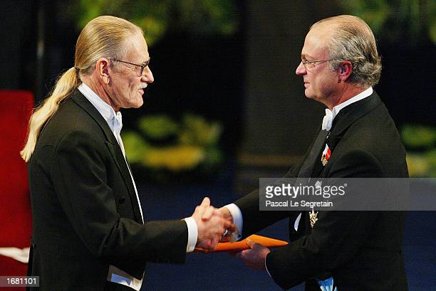 American Dr Vernon LSmith shakes hands with King Carl XVI Gustaf of Sweden as he receives the prize in Econonmic Sciences in memory of Alfred Nobel...