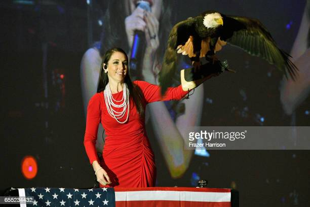 American Eagle Foundation Director of Operations Laura Sterbens holds a bald eagle named Challenger as the American national anthem is performed...