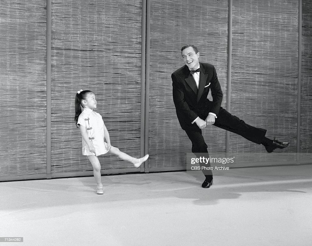 American entertainer Gene Kelly (1912 - 1996) dances with Cherylene Lee on a television special called 'The Gene Kelly Pontiac Special,' April 24, 1959. Kelly is dressed in a suit and tie, while young Lee wears a Cheongsam dress.