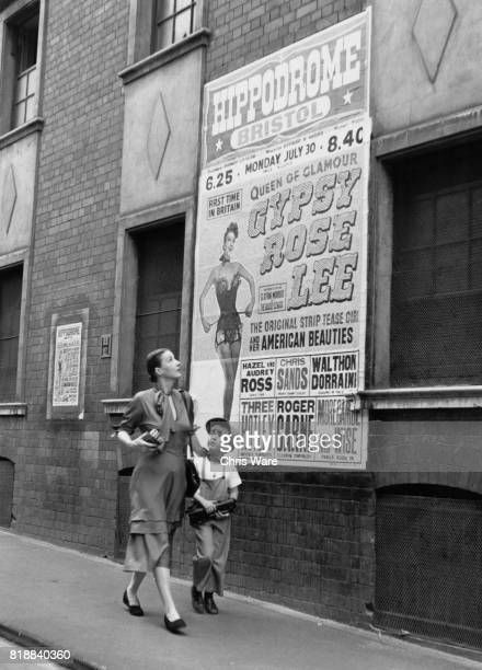 American entertainer Gypsy Rose Lee passes a poster advertising her show with her son Eric in Bristol UK 1951