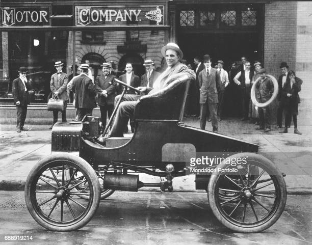 American entrepreneur Henry Ford driving one of his first cars on the road in front of his own factory Detroit 1905