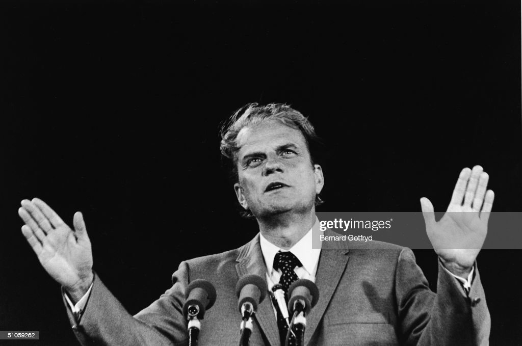 American evangelicist Reverend Billy Graham stands palms outstretched behind a three microphones and gazes upwards Shea Stadium New York 1970