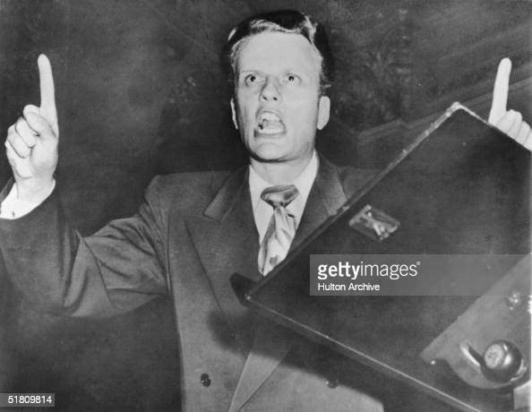 American evangelist Billy Graham points upward as he preaches early 1950s