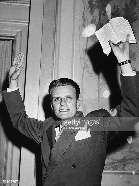 American evangelist Billy Graham raises his hands and a Bible in the air mid 1950s