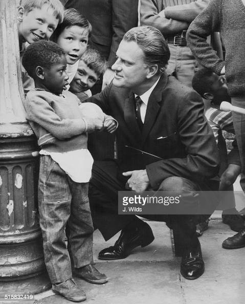 American evangelist Billy Graham talking to a group of children during a visit to Brixton Parish Church London June 12th 1966