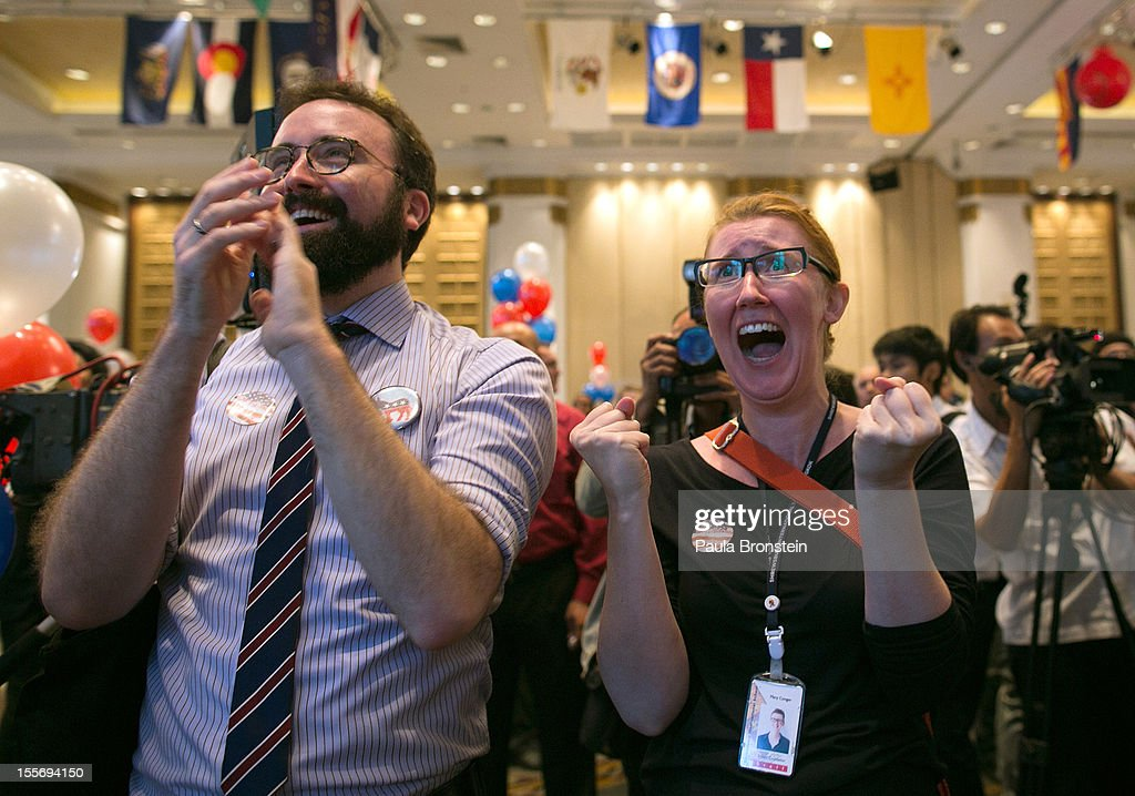 American expats Colin Cheney from Boston (L) and Mary Conger from Minnesota react as President Barak Obama wins his re-election bid at the U.S embassy election watch party November 7, 2012 in Bangkok, Thailand. Obama won with 303 electoral votes to Romney's 206 with Florida votes still not included in the total.