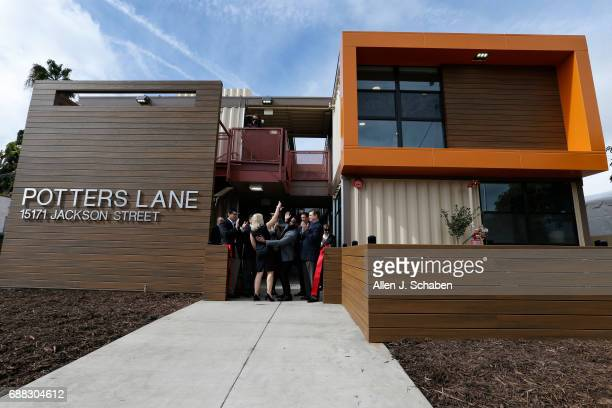 American Family Housing chief executive Donna Gallup center with hand up celebrates with dignitaries during the ceremonial ribboncutting ceremony at...