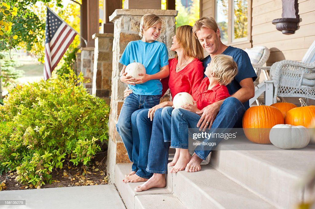 American family on home porch with happy smiles in Autumn : Stock Photo