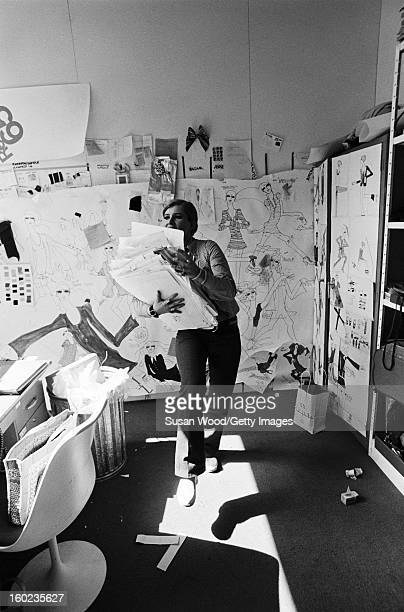 American fashion designer Betsey Johnson carries a pile of sketches in her studio New York New York September 6 1966