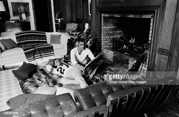 American fashion designer Ralph Lauren and his wife therapist Ricky read a newspaper beside the fireplace in their home East Hampton New York...