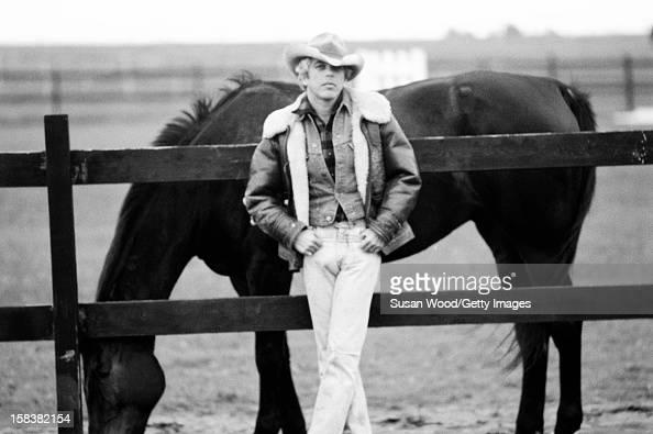 American fashion designer Ralph Lauren poses beside a horse near his home East Hampton in November 1977