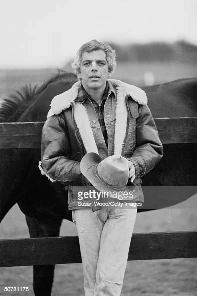 American fashion designer Ralph Lauren poses outdoors leaning against a wooden fence and holding his hat with horses behind him 1970s