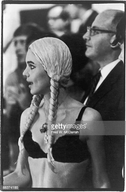 American fashion model and actress Edie Sedgwick dressed in a blond wig with long braids and a black bra stands near the swimming pool in the Hudson...