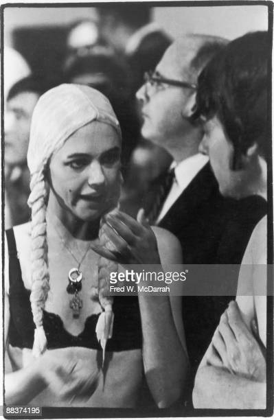 American fashion model and actress Edie Sedgwick dressed in aa blond wig with long braids and a black bra talks to an unidentified man near the...