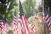American soldier in uniform saluting while standing in a field of American flags