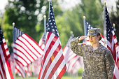 Beautiful  young American female soldier saluting in front of Stars and Stripes