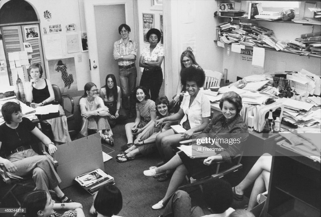 American feminist, journalist, and activist Gloria Steinem (at rear, right side, sitting on a white chair) at her desk during a staff meeting for Ms. magazine, New York City, 1975.