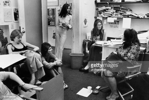 American feminist journalist and activist Gloria Steinem sits at her desk during a staff meeting for MS Magazine New York City 1975