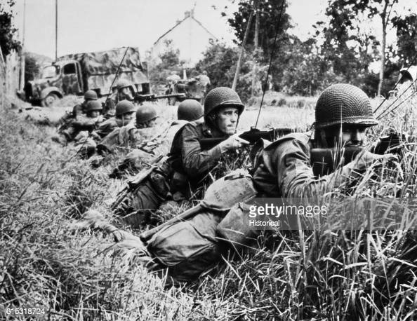 American fighting men pressing closely on the heels of retreating Germans in the Battle of Normandy take cover in a ditch at St SauveurleVicomte as...