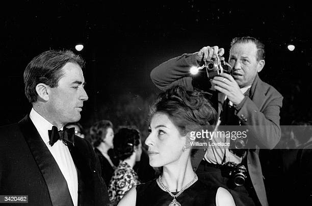 American film actor Gregory Peck and his wife Veronique being photographed at the Oscars ceremony in Hollywood 11th April 1962 The photographer is...
